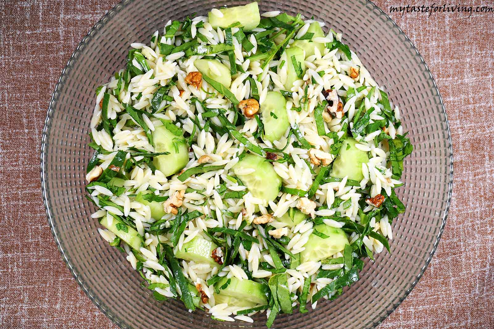 Fresh salad prepared with orzo (also called kritharaki , arpa fide or risoni), cucumbers, spinach, parsley and walnuts, seasoned with crushed garlic, freshly squeezed lemon juice and extra virgin olive oil.