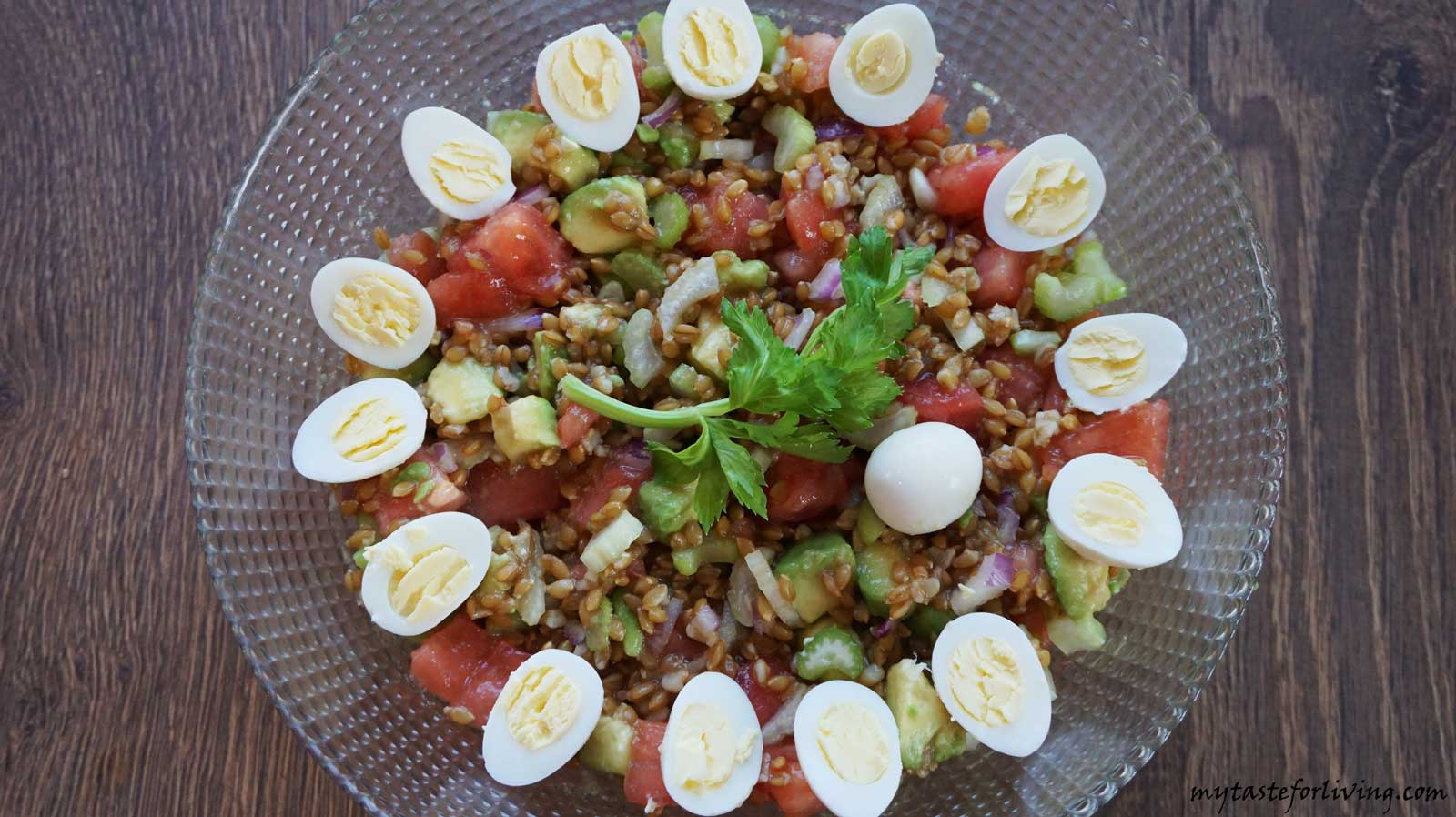 Delicious salad of einkorn with avocado, celery and tomatoes.